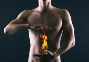 Acid reflux man holding flames over stomach