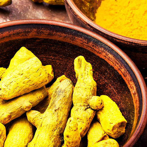 Turmeric powder and root turmeric in a bowl. Turmeric Spice